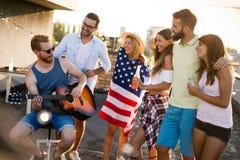 Amis célébrant le 4ème des vacances de juillet Images stock