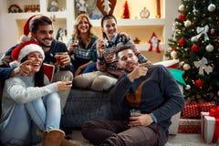 Amis célébrant Noël à la maison Image libre de droits
