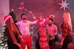 Amis célébrant Noël ou la soirée du Nouveau an à la maison Photos libres de droits