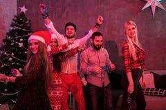 Amis célébrant Noël ou la soirée du Nouveau an à la maison Image libre de droits