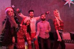 Amis célébrant Noël ou la soirée du Nouveau an à la maison Images libres de droits