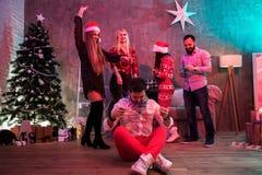 Amis célébrant Noël ou la soirée du Nouveau an à la maison Photographie stock libre de droits