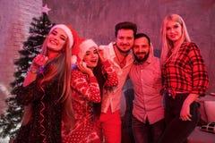 Amis célébrant Noël ou la soirée du Nouveau an à la maison Image stock
