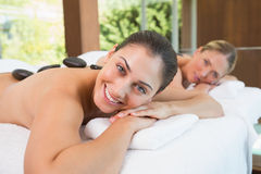 Amis calmes se trouvant sur des tables de massage avec les pierres chaudes sur leurs dos Image libre de droits
