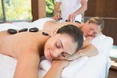 Amis calmes se trouvant sur des tables de massage avec les pierres chaudes sur leurs dos Images stock