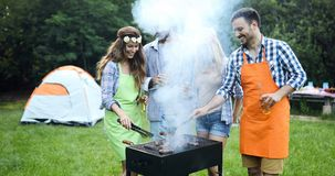 Amis campant et ayant un barbecue Photos stock