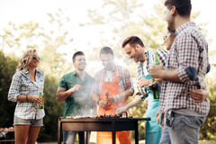 Amis campant et ayant un barbecue Photos stock