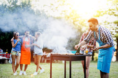 Amis campant et ayant un barbecue Photographie stock libre de droits