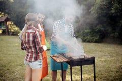 Amis campant et ayant un barbecue Images libres de droits