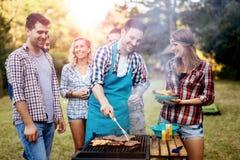 Amis campant et ayant un barbecue Photographie stock