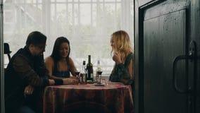 Amis causant à la table Alcool de boissons sur la terrasse de la maison de campagne rire clips vidéos