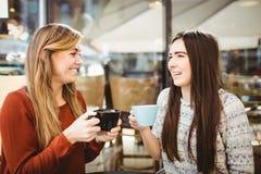Amis causant au-dessus du café Photos stock