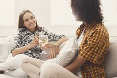 Amis causant avec des verres à vin à la maison Photo stock
