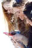 Amis causant avec leurs smartphones Photos libres de droits