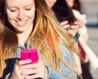Amis causant avec leurs smartphones Photographie stock libre de droits