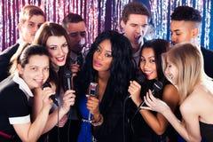 Amis chantant dans des microphones à la partie de karaoke Photographie stock libre de droits