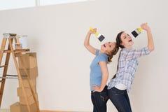 Amis chantant dans des pinceaux par l'échelle dans une nouvelle maison Image stock