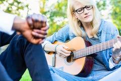 Amis chantant des chansons en parc ayant l'amusement ensemble Photos stock
