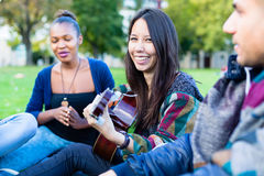 Amis chantant des chansons en parc ayant l'amusement ensemble Images stock