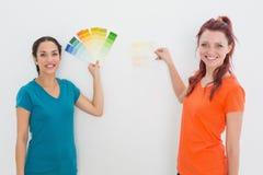 Amis choisissant la couleur pour peindre une salle Photographie stock