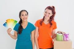Amis choisissant la couleur pour peindre une salle Photos stock