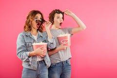 Amis choqués de femmes mangeant le film de montre de maïs éclaté Photos stock