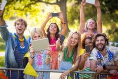 Amis cliquant sur des photos de leurs téléphones portables et comprimé numérique Image stock