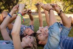 Amis cliquant sur le selfie aux téléphones portables Photo libre de droits