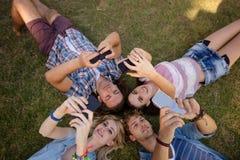 Amis cliquant sur le selfie aux téléphones portables Images stock