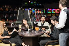 Amis commandant le dîner à un casino Images libres de droits