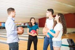 Amis communiquant tout en ayant l'amusement au bowling Image stock