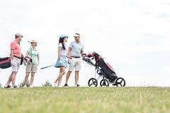 Amis communiquant tout en marchant au terrain de golf contre le ciel clair Photos stock