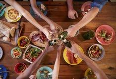Amis composant un pain grillé à une table de dîner, aérienne, fin Photographie stock libre de droits