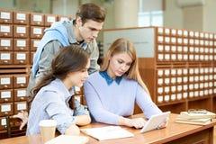 Amis concentrés employant le wifi dans la bibliothèque Photographie stock libre de droits