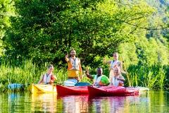 Amis conduisant avec le kayak sur la rivière Image libre de droits