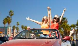 Amis conduisant dans la voiture au-dessus de la plage de Venise Image stock