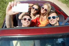 Amis conduisant dans la voiture de cabriolet et prenant le selfie Photo stock