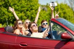 Amis conduisant dans la voiture de cabriolet et prenant le selfie Photos stock