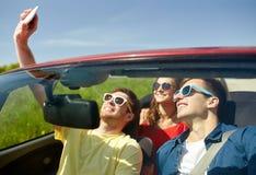 Amis conduisant dans la voiture de cabriolet et prenant le selfie Image libre de droits