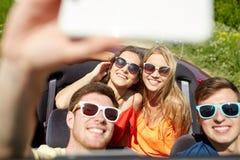 Amis conduisant dans la voiture de cabriolet et prenant le selfie Images libres de droits