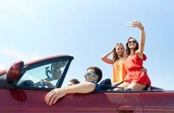 Amis conduisant dans la voiture de cabriolet et prenant le selfie Photo libre de droits
