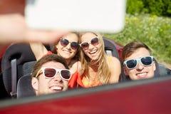 Amis conduisant dans la voiture de cabriolet et prenant le selfie Photographie stock libre de droits