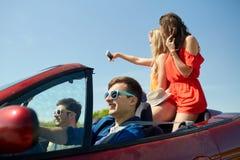 Amis conduisant dans la voiture de cabriolet et prenant le selfie Photographie stock