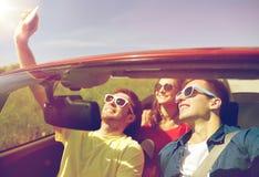 Amis conduisant dans la voiture de cabriolet et prenant le selfie Images stock