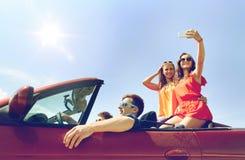 Amis conduisant dans la voiture de cabriolet et prenant le selfie Photos libres de droits