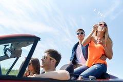 Amis conduisant dans la voiture et les bulles de soufflement Photographie stock libre de droits