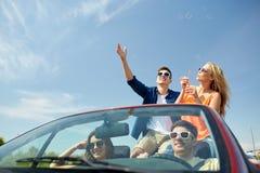 Amis conduisant dans la voiture et les bulles de soufflement Photographie stock