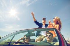 Amis conduisant dans la voiture et les bulles de soufflement Photos libres de droits