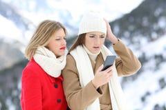 Amis confus avec un téléphone intelligent en hiver Photo stock