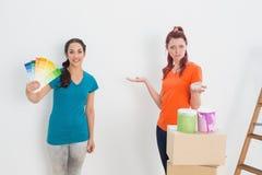 Amis confus choisissant la couleur pour peindre une salle Images libres de droits